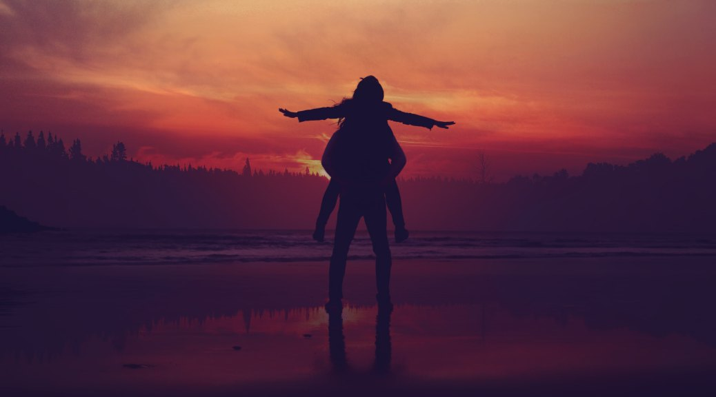 girl on guys shoulders in the sunset silhouette