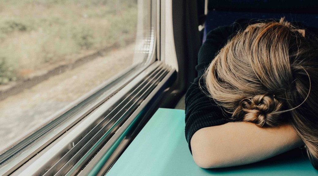 woman laying head down on table by window