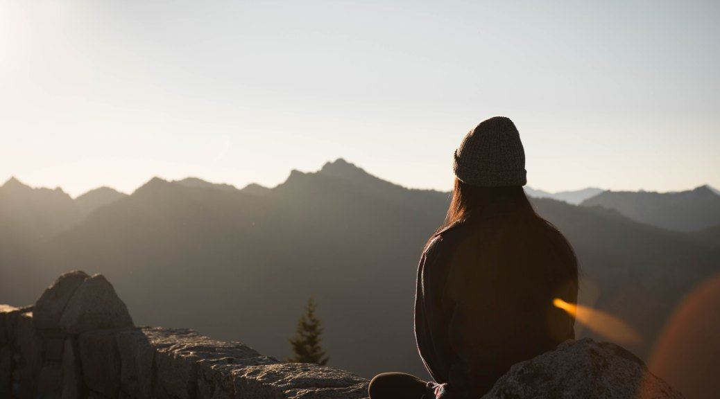 girl sitting in mountains with sunshine