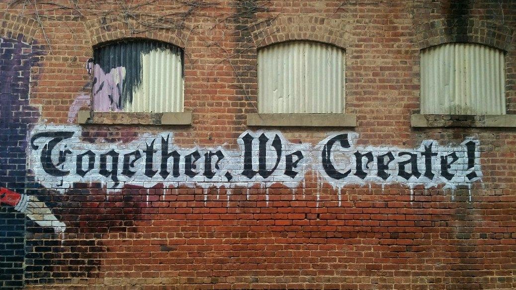 together, we create graffiti on brick wall